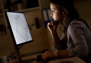 Young business woman working late in office.She works late into the night looking at monitor.